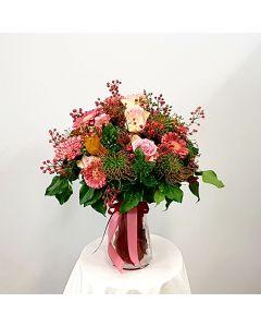 Mazzo di gerbere rosa, rose e cordifolio con vaso di vetro circolare